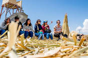 group of tourists sitting on the islands of the uros